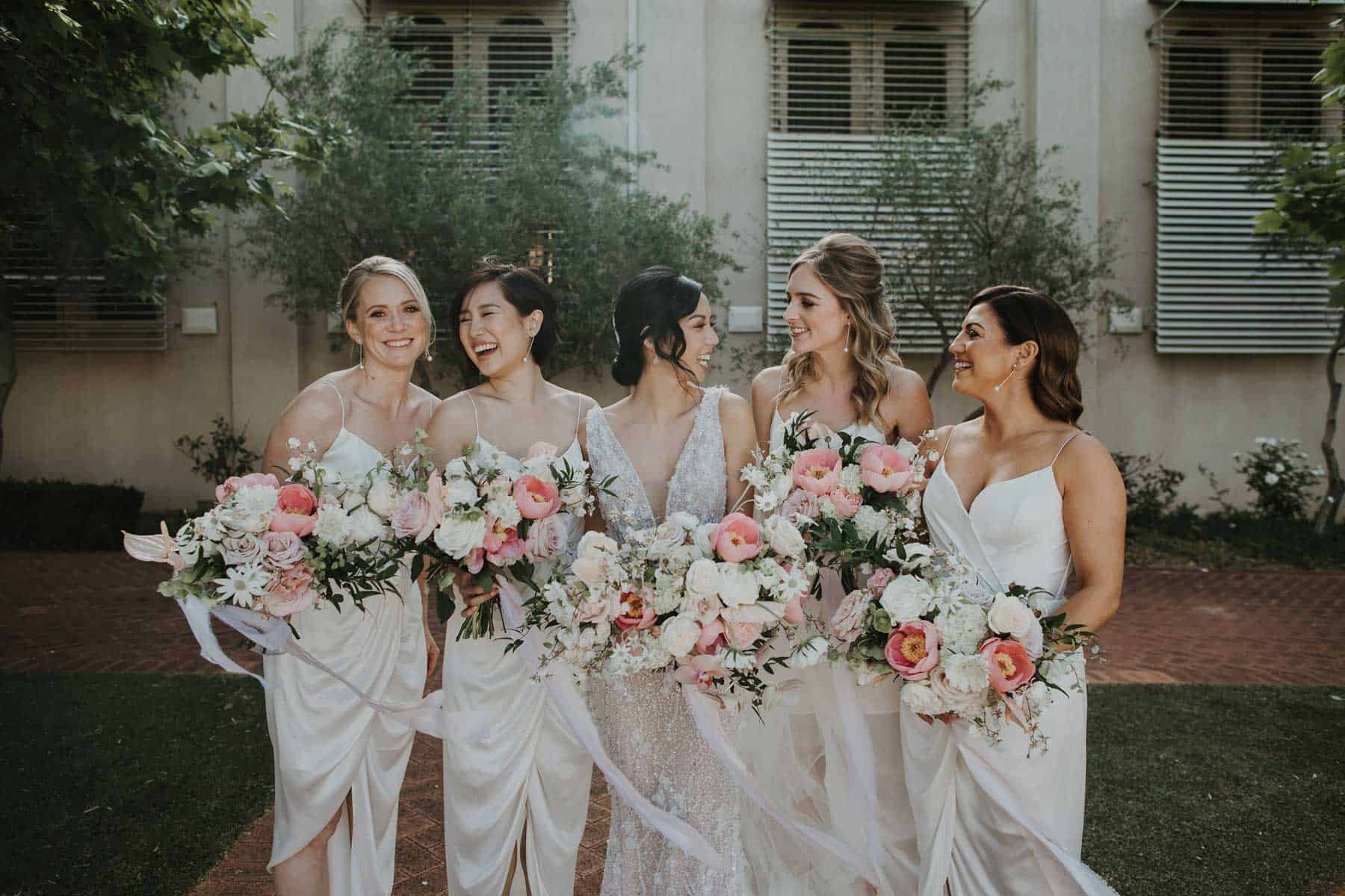 bridesmaids in white with soft pink bouquets
