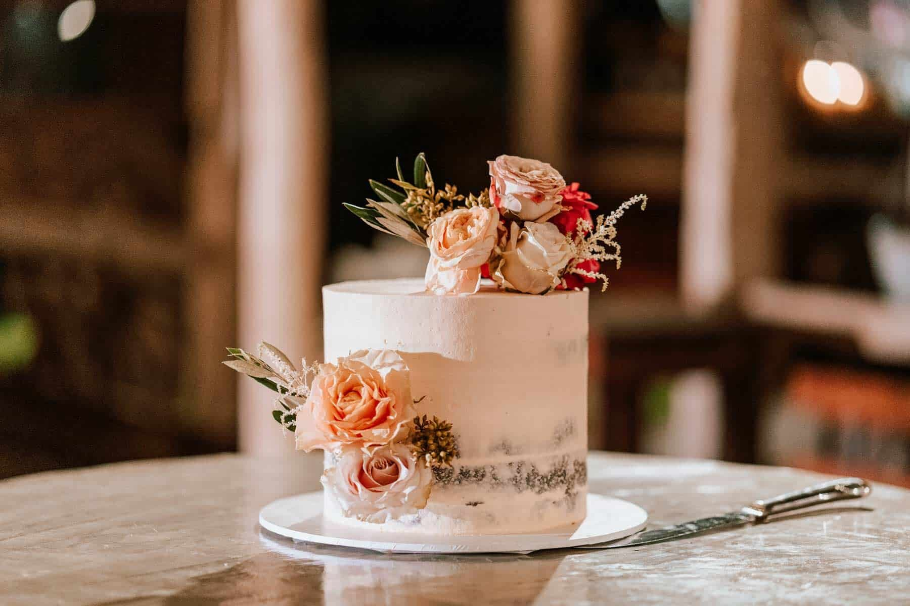 simple wedding cake with peach-toned flowers
