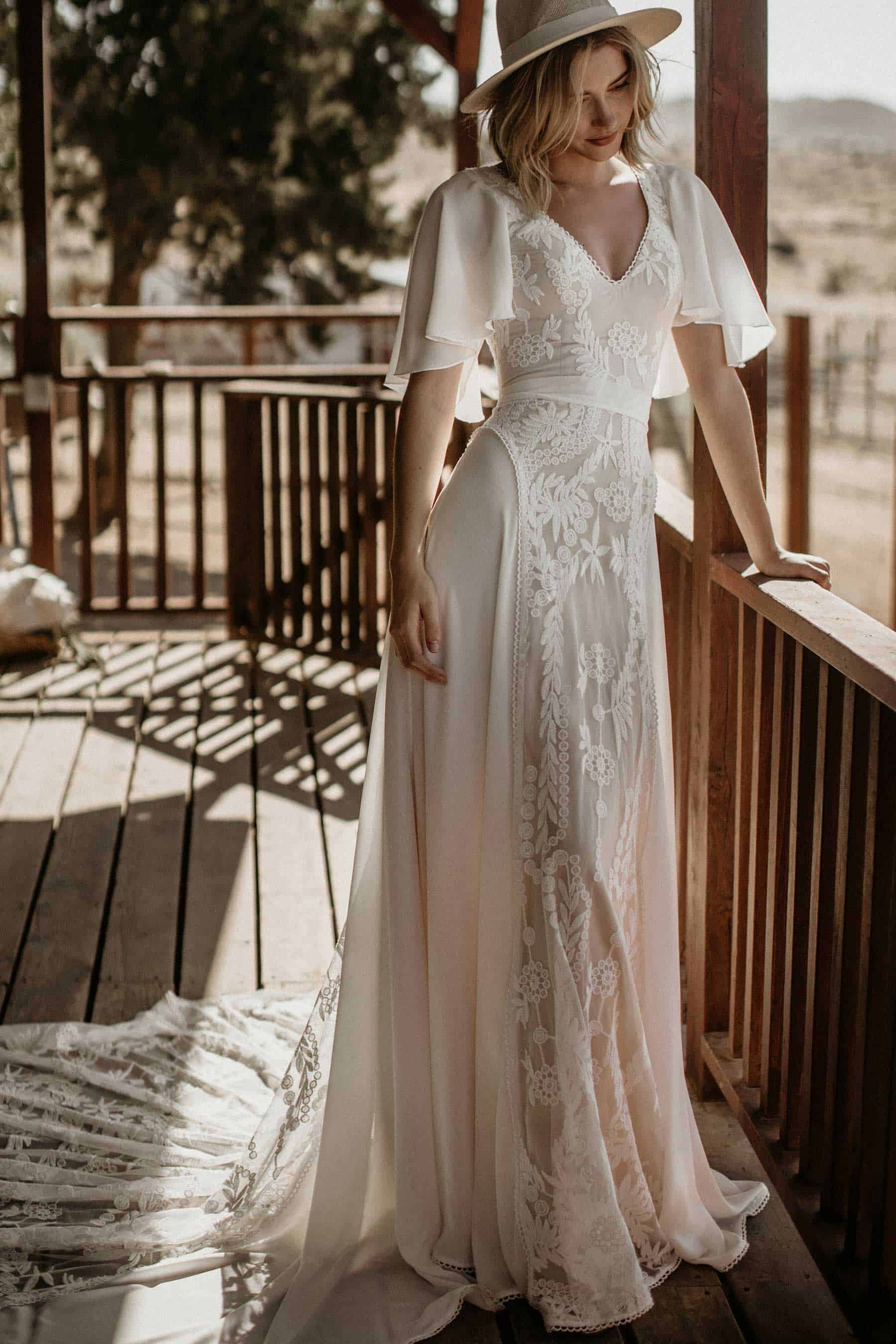 indie bride in cape-sleeve wedding dress and hat