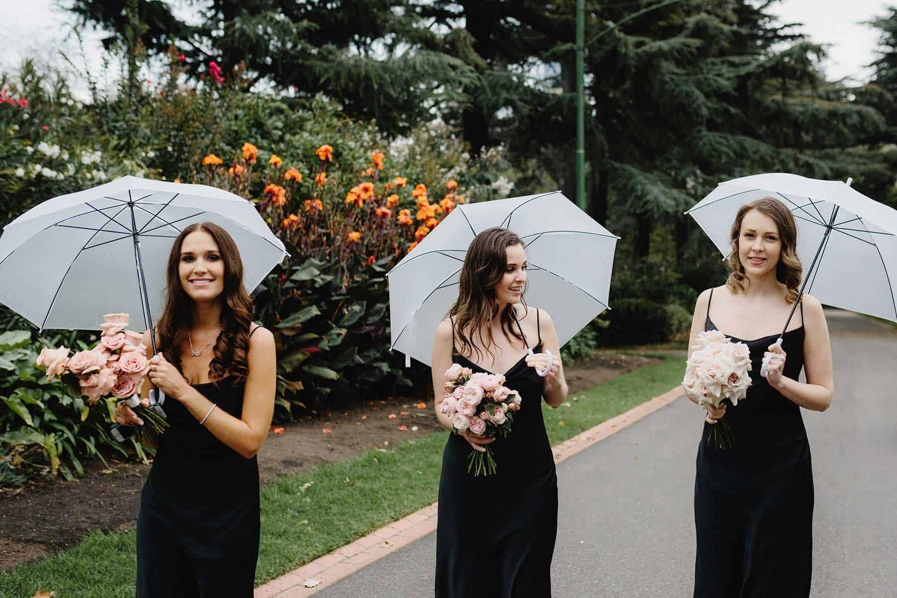 bridesmaids in black dresses with umbrellas