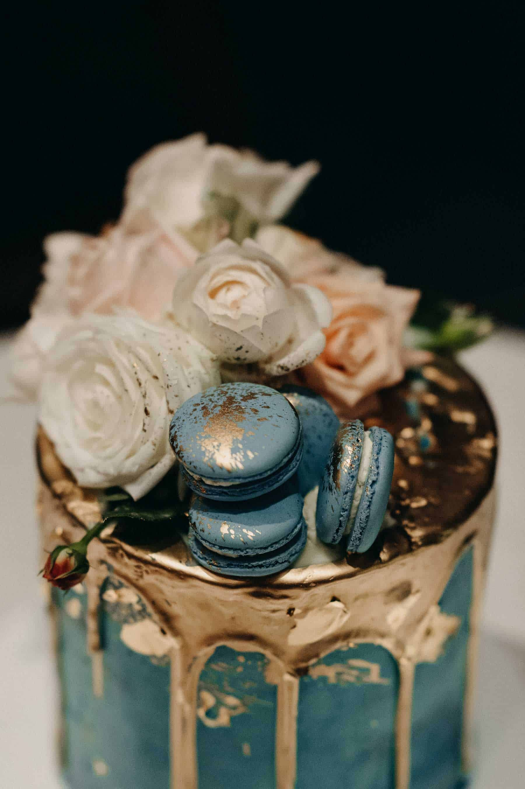 blue wedding cake with gold drip and macarons