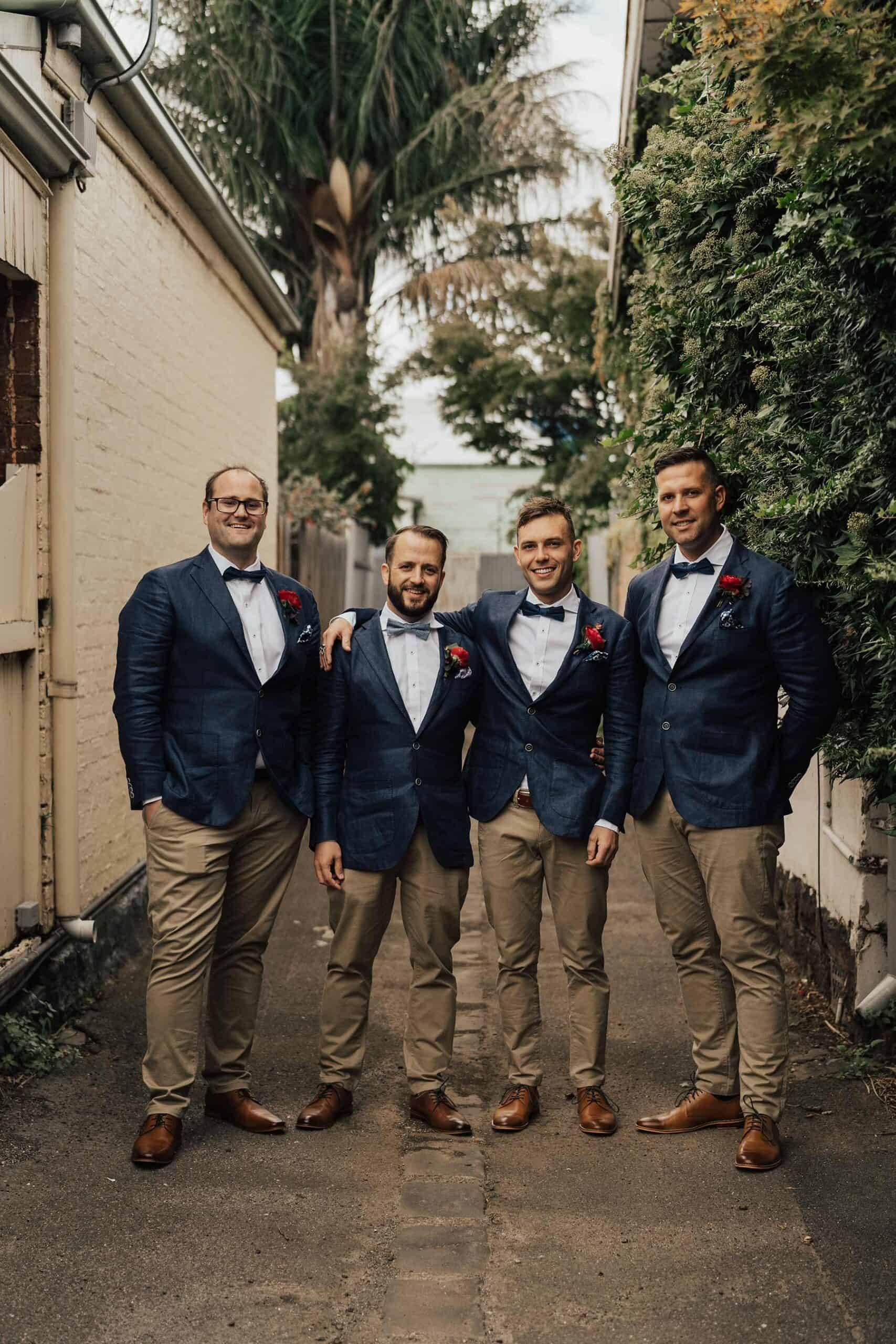 groomsmen in tan chinos and navy blazers